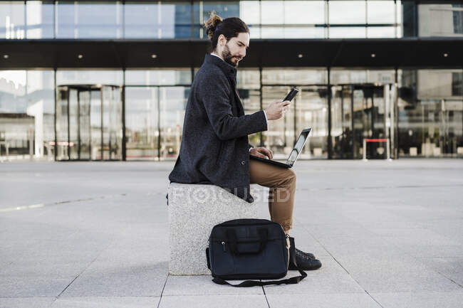 Businessman with laptop using mobile phone while sitting on bench — Stock Photo