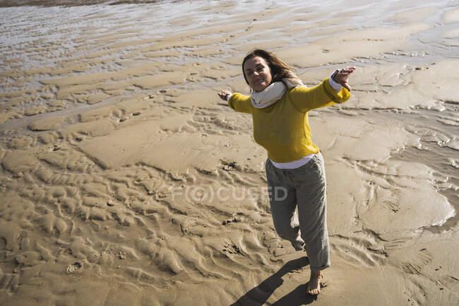 Donna spensierata che balla in spiaggia durante la giornata di sole — Foto stock