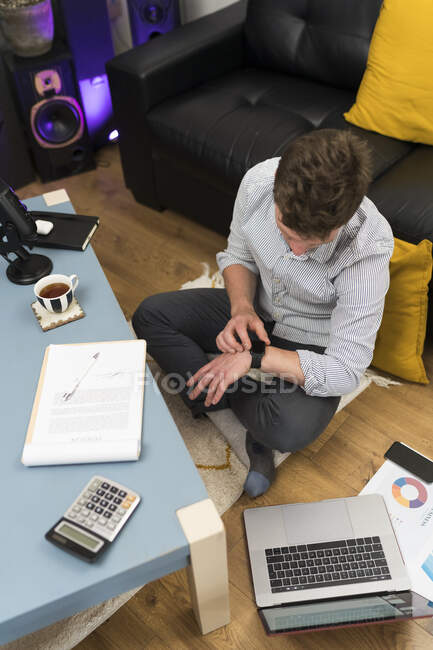 Businessman checking smart watch while sitting at home — стокове фото