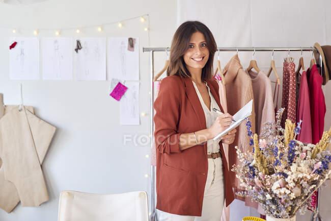 Sorrindo designer de moda bonita escrevendo em diário, enquanto em pé contra rack de roupas no atelier — Fotografia de Stock
