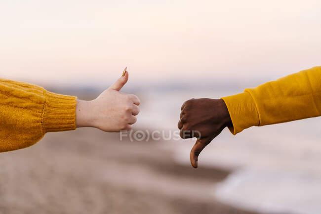 Mujer y hombre mostrando golpes arriba y abajo gesto en la playa - foto de stock