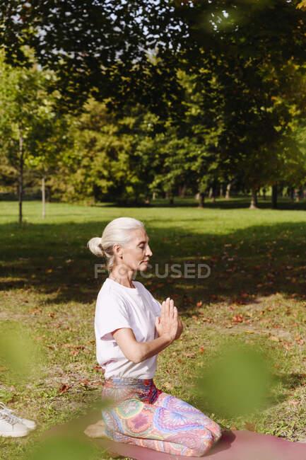 Зрелая женщина занимается йогой на траве в общественном парке — стоковое фото