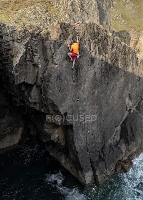 Maduro macho escalador de roca llegar en la parte superior del acantilado - foto de stock