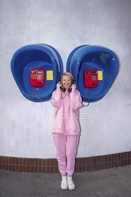 Посміхнена молода жінка з рожевим волоссям у рожевій пов'язаній сорочці, що стоїть перед телефонними будками. — стокове фото