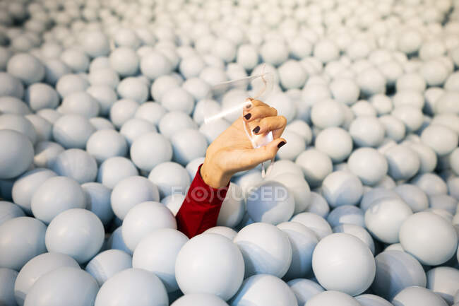 Hand of young woman holding face shield in ball pit - foto de stock