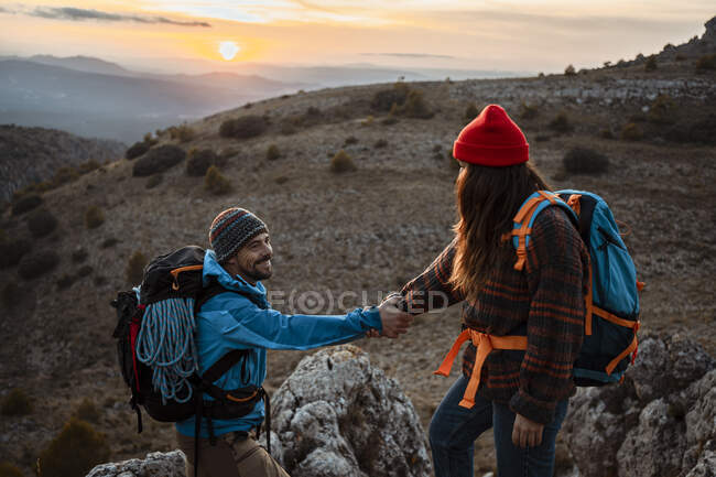 Fidanzata aiutare fidanzato a scalare montagna rocciosa durante il tramonto — Foto stock