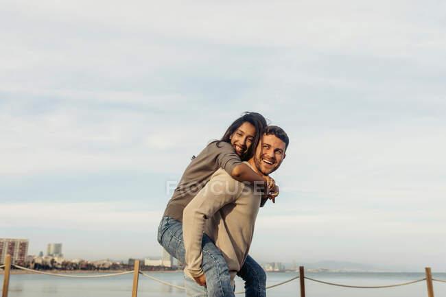 Счастливый бойфренд катается на спине с подружкой, стоящей у моря на фоне неба — стоковое фото