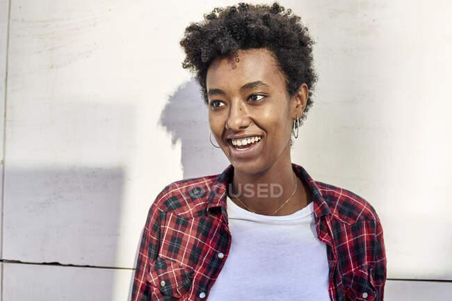 Усміхнена молода африканка, що дивиться на білу стіну. — стокове фото