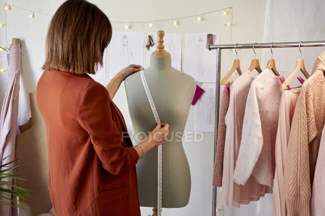 Жіночий модний підприємець вимірює модель майстра одягу за стійкою для одягу в дизайнерській студії — стокове фото