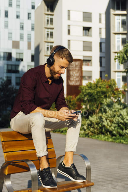 Businessman wearing headphones using smart phone while sitting on bench — Stock Photo
