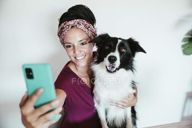Mujer sonriente tomando selfie con Border Collie contra la pared en casa - foto de stock