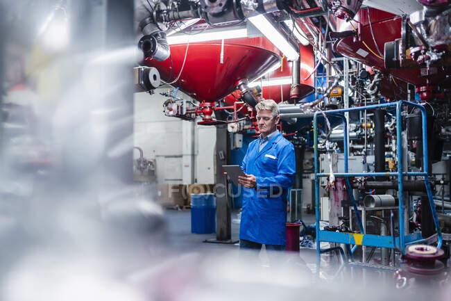 Engenheiro masculino trabalhando em tablet digital em pé contra equipamentos de máquinas na fábrica — Fotografia de Stock