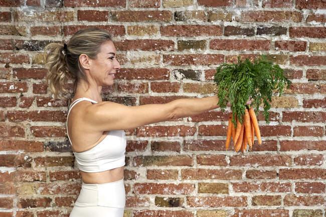 Sorrindo mulher madura segurando um monte de cenouras na cozinha por parede de tijolo — Fotografia de Stock