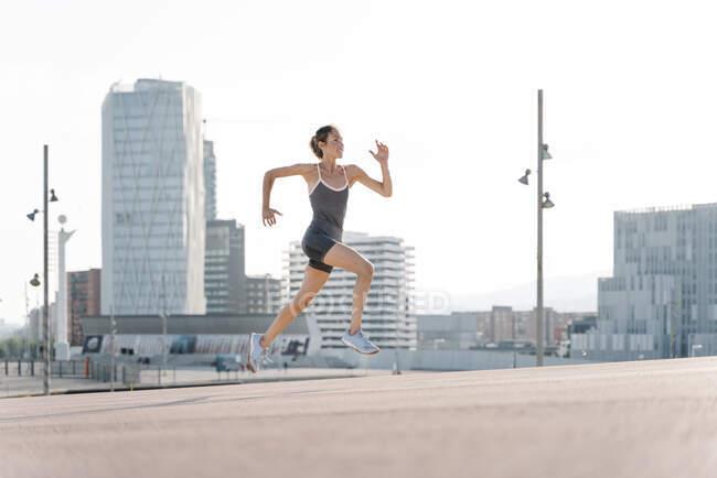 Улыбающаяся спортсменка вбегает в город — стоковое фото