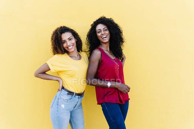 Feliz pareja lesbiana de pie contra la pared amarilla - foto de stock