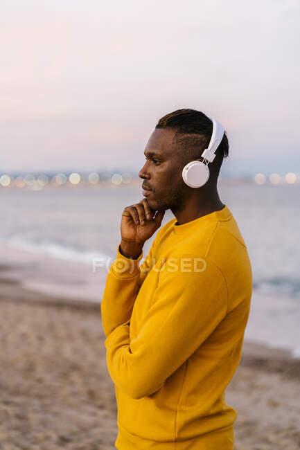 Mittlerer erwachsener Mann trägt Kopfhörer und hört Musik, während er am Strand steht — Stockfoto