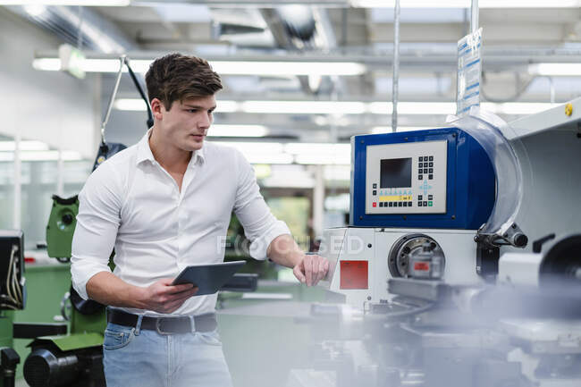 Male engineer examining manufacturing equipment while holding digital tablet in factory — стоковое фото