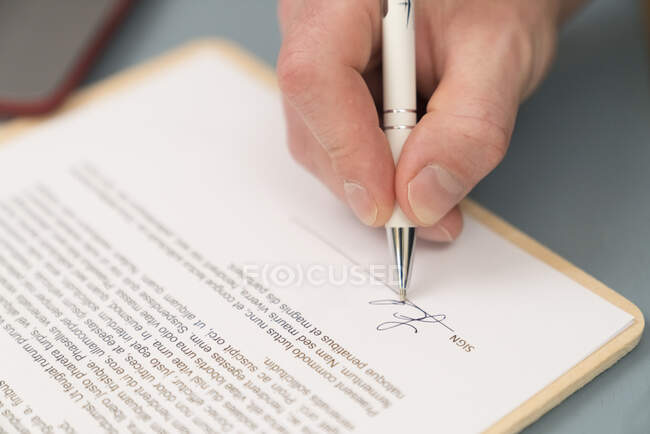 Close-up of businessman giving signature on contract paper at home — стокове фото