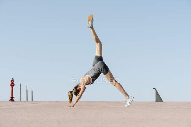 Взрослая спортсменка, занимающаяся йогой на ясном небе — стоковое фото