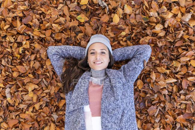 Senderista sonriente con las manos detrás de la cabeza acostada sobre las hojas de otoño en Cannock Chase woodland - foto de stock
