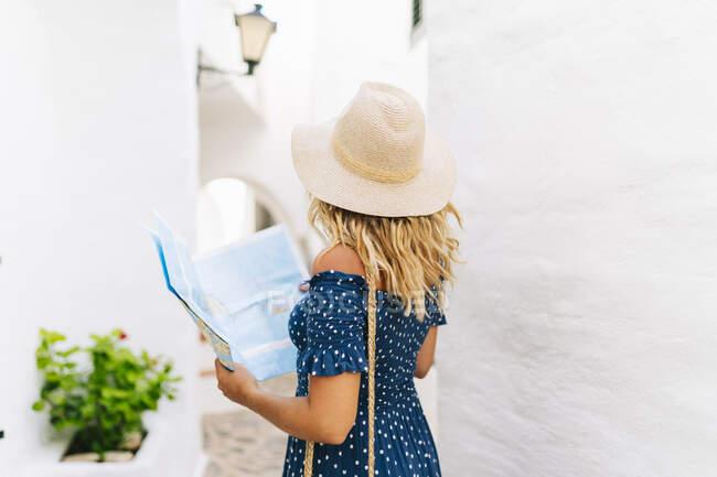 Mature woman wearing hat with map standing in Binibeca village, Minorca, Spain - foto de stock