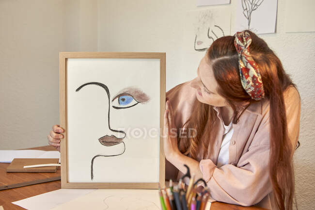 Female artist showing drawing art picture frame against wall at home — Stock Photo