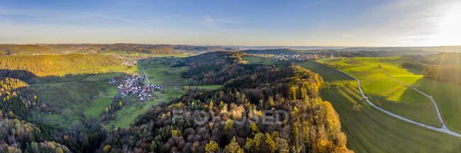 Drone vista del villaggio circondato dalla foresta autunnale all'alba — Foto stock