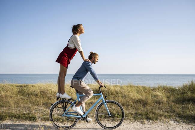 Namorada desfrutando de passeio com o homem enquanto está de pé na bicicleta contra o céu limpo — Fotografia de Stock