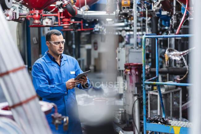 Técnico masculino usando tablet digital enquanto trabalhava na fábrica — Fotografia de Stock