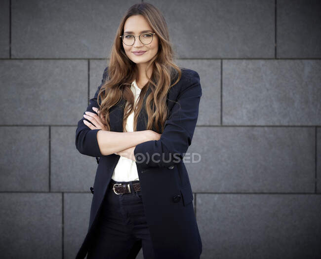 Confident business professional with arm crossed standing against concrete brick wall — Stock Photo