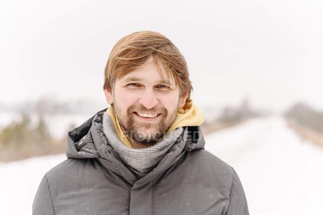 Крупный план портрета улыбающегося среднего взрослого мужчины на фоне ясного неба зимой — стоковое фото