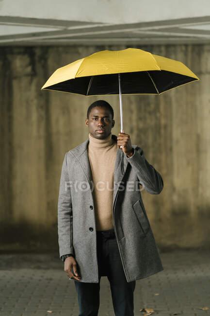 Чоловік тримає жовту парасольку, стоячи навпроти стіни. — стокове фото