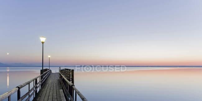 Germania, Baviera, cielo limpido sul molo di legno sulla riva del lago Chiemsee al tramonto — Foto stock