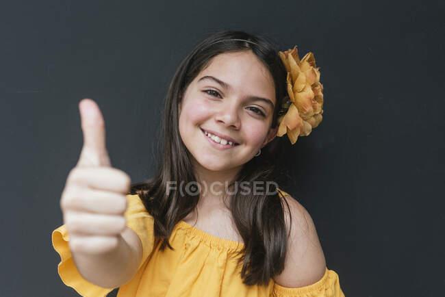 Nahaufnahme eines lächelnden Mädchens mit gelbem Stirnband, das die Daumen vor schwarzem Hintergrund zeigt — Stockfoto