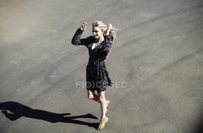 Bela jovem mulher sorrindo enquanto caminhava na estrada durante o dia ensolarado — Fotografia de Stock