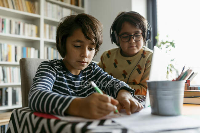 Boy writing notes while male friend sitting beside him at home — Stock Photo