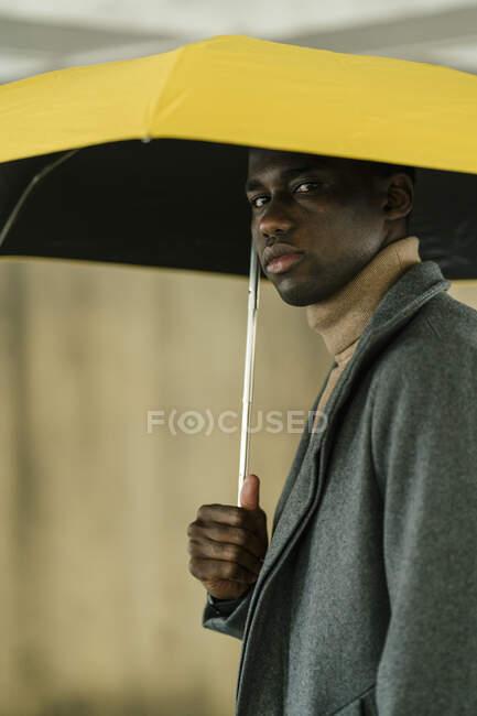 Homem com guarda-chuva olhando ao ar livre — Fotografia de Stock