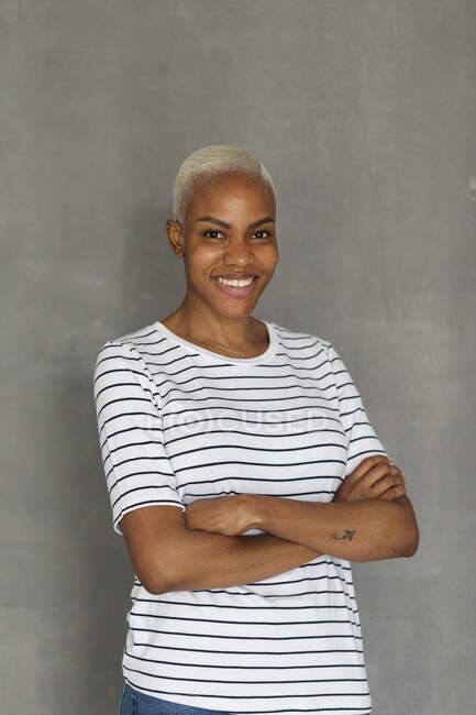 Mujer sonriente con camisa a rayas de pie delante de fondo gris con los brazos cruzados - foto de stock