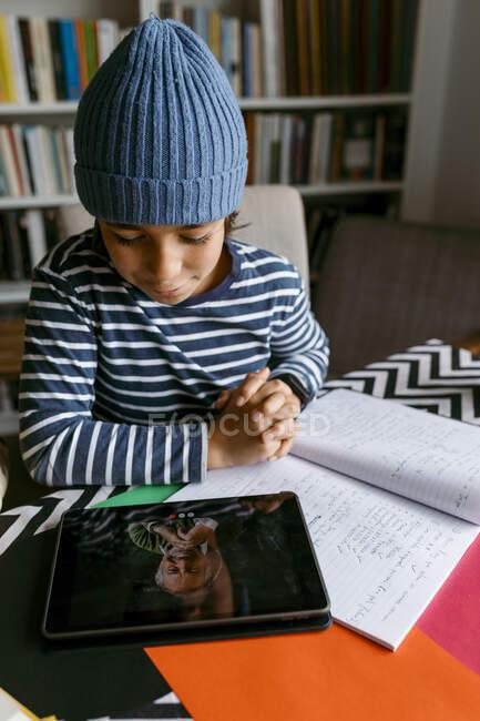 Garçon communiquant avec le professeur à la classe de l'école à domicile dans le salon — Photo de stock