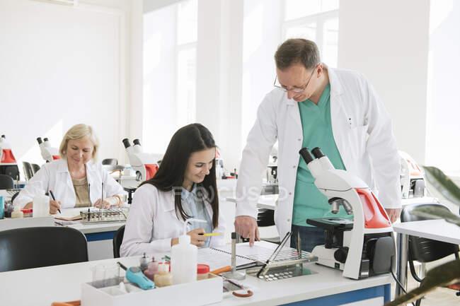 Студенти та викладачі, які працюють на уроках науки — стокове фото