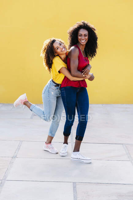 Посміхнена лесбіянка обнімає подругу ззаду з жовтою стіною. — стокове фото