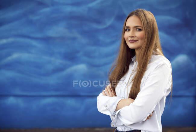 Безробітна жінка стоїть зі схрещеними руками проти синьої стіни. — стокове фото