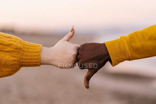 Чоловік і жінка жестикулюють з пальцями вгору і вниз на пляжі. — стокове фото