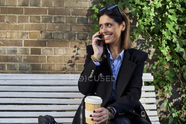 Donna d'affari sorridente con tazza di bambù che parla sullo smart phone mentre siede sulla panchina — Foto stock