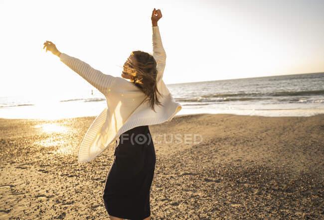 Donna spensierata che balla sulla spiaggia contro il cielo durante la giornata di sole — Foto stock
