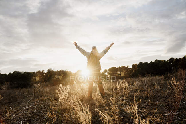Senior male hiker with arms raised standing in filed during sunset — Stock Photo