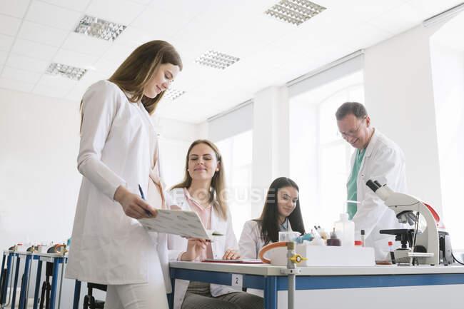 Estudiantes y profesores de batas blancas discutiendo en clase de ciencias - foto de stock