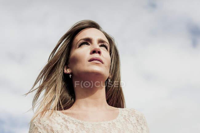 Close-up de mulher pensativa com cabelo loiro contra o céu nublado — Fotografia de Stock