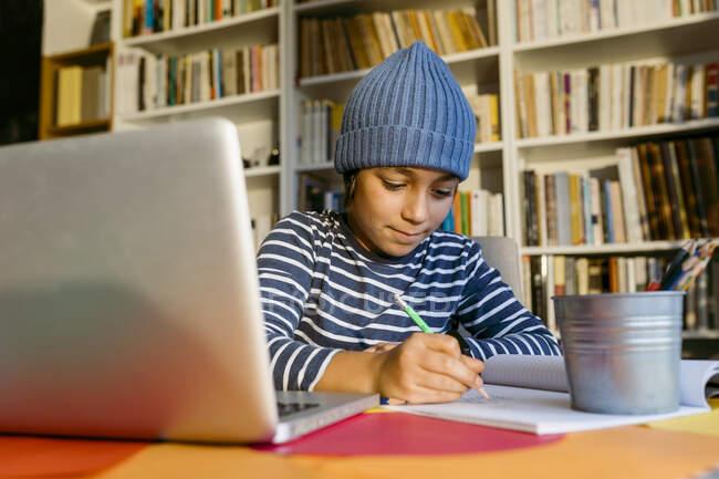Garoto sorrindo usando chapéu de malha escrevendo no livro enquanto sentado em casa — Fotografia de Stock