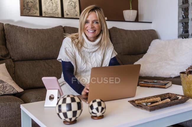Щаслива жінка-порадник сидить з ноутбуком на дивані на робочому місці. — стокове фото